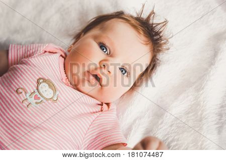Cute 3 months old baby girl in pink lying down on a white bed at home looking at camera. Big open eyes. Infant napping in bed. Healthy little kid shortly after birth