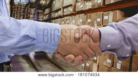 Digital composite of Close-up of business people shaking hands in warehouse
