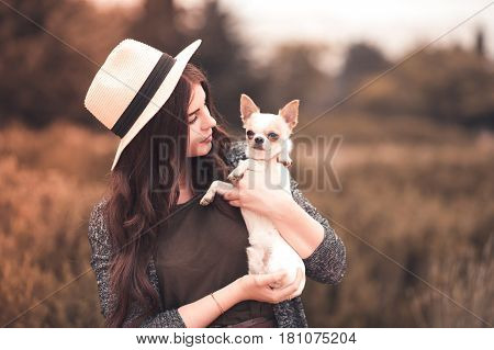 Stylish girl 24-29 year old holding chihuahua puppy wearing summer hat outdoors. Friendship. 20s.