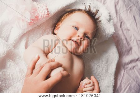 Close-up portrait of cute happy smiling baby girl lying down on bed. Mother is holding her newborn baby. Small daughter and mum