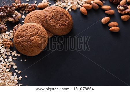 Healthy oat cookies made of wholegrain oat and nuts on dark table background, free copy space. Flat lay, mockup, template, objects, nobody