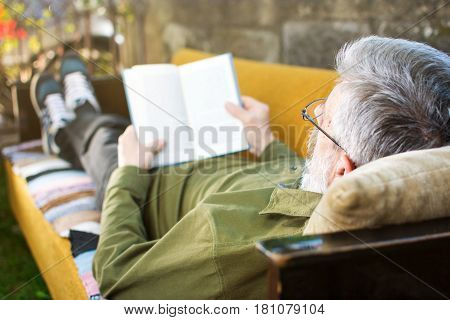 Senior Man Reading Lying On Bed In The Yard
