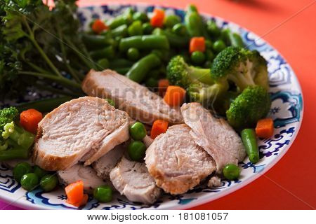 Healthy food, diet nutrition. Green steamed vegetables and slices of chicken fillet on bright geometric background, closeup, copy space