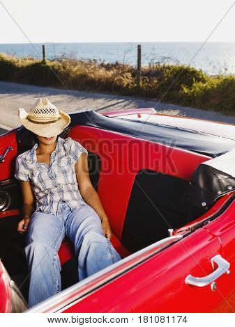 Mixed race woman sleeping in back of red convertible
