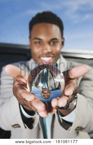 African businessman holding crystal ball