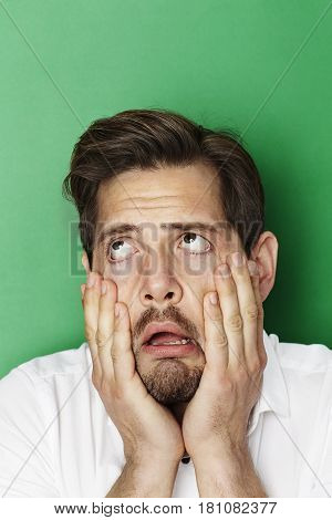 Man with hands in face  groaning in green studio