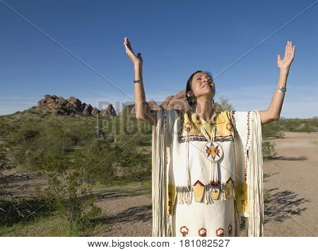 Native American woman in traditional clothing with arms raised