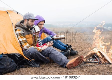 Family Drinking Tea Near Burning Fire