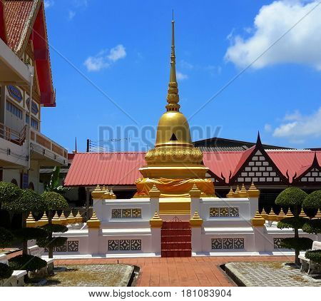 small gold plated bell-shaped chedi tower on a raised platform at a Buddhist temple in Songkhla, Thailand
