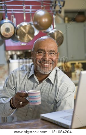 African man with laptop drinking coffee in kitchen