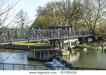 People Crossing The River Cam At An Old Iron Pedestrian Bridge