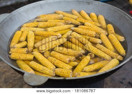 Country fair food cooking. Corns boiled outdoors in big metal bowl. Cookout vegetable meals. Fresh organic, healthy snack, corncobs cooked on grill flame. Street fast food.