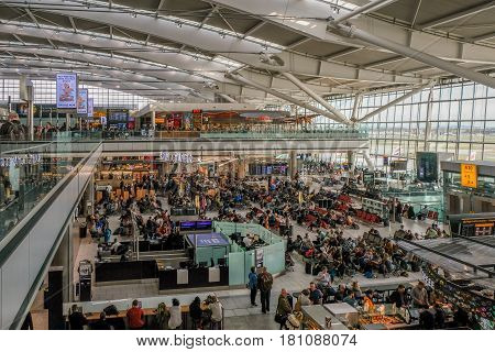 LONDON UK - MARCH 7 2017: Heathrow Airport Terminal 5 passengers waiting to get gate information mid-morning.