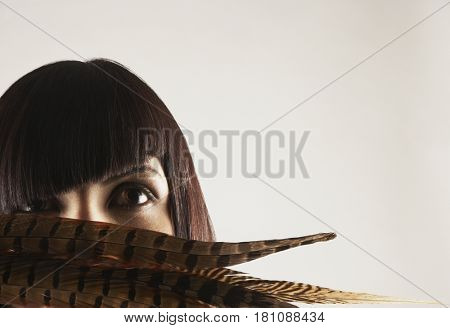 Hispanic woman with feather in front of face