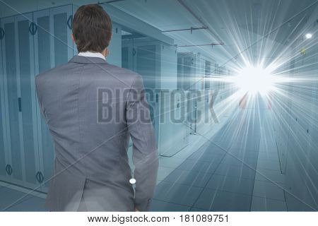 Digital composite of Digital composite image of businessman looking at light at data center
