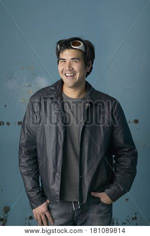 Asian man smiling with hands in pockets