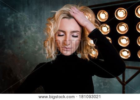 portrait of young stylish beatiful attractive curly girl in black sweater on the stage with lamp and soffits in the loft