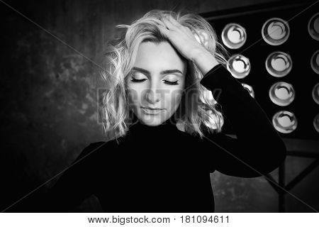 Black and white portrait of young stylish beautiful attractive curly girl in black sweater on the stage with lamp and soffits in the loft