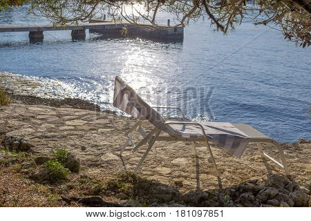 Empty lounger on the rocky beach with blue sea background