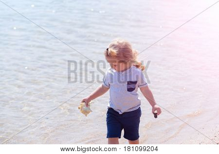 marine kid fashion. happy cute baby boy small little child with blond hair smiling with seashell or marine shell in hand on sunny day on bokeh sea water background. Idyllic summer vacation