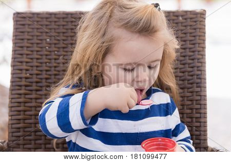 long blonde stylish hair adorable baby boy small little child in blue striped clothes eating tasty ice cream frozen pink dessert with spoon on chair in outdoor cafe sunny day