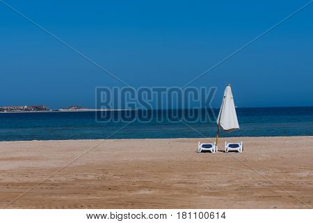 Idyllic tropical beach with golden sand sun beds and white umbrella at beautiful blue sea shore coast on bright sunny day on cloudless sky background. Summer vacation in paradise traveling
