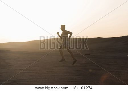workout sport and marathon. man runner or fit male athlete running in desert sand dune at mountain in sun ray at sunset sunrise outdoor on white sky background. sprinting healthy lifestyle success
