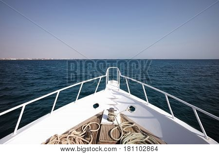 White boat or ship vessel heading to horizon in sea or ocean water on sunny day on blue sky background. Idyllic summer vacation traveling and transport sport hobby fishing and yachting