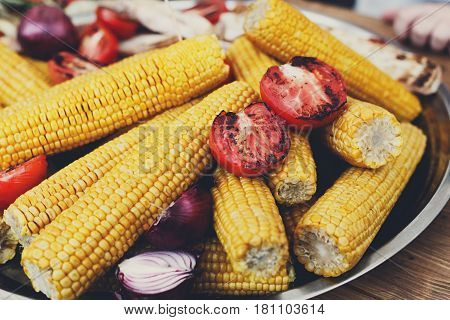 Vegan bbq party. Barbecue corns and tomatoes closeup. Cookout vegetable food. Fresh organic, healthy vegetarian snack, corncobs roasted on grill. Street fast food. Tasty natural meals