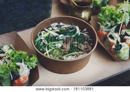 Thai take away street food, tom yam kung soup. Traditional hot spicy curry soup with meat, greenery and noodles, outdoor fast food market