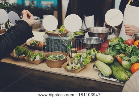 Street food, vendor sold healthy snacks. Vegetable salads in kraft paper plates outdoors at local market place, thai food festival