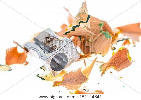 Old Rusty Metal Pencil Sharpener And Different Colour Shavings.