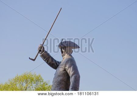 Statue of Chelsea pensioner waving stick with blue sky in background