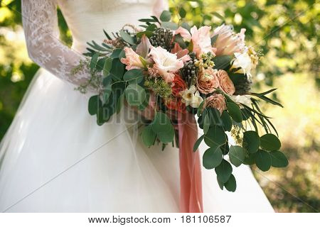 Wedding gentle disheveled bouquet of peach shades with pink ribbon. Horizontal photo side view