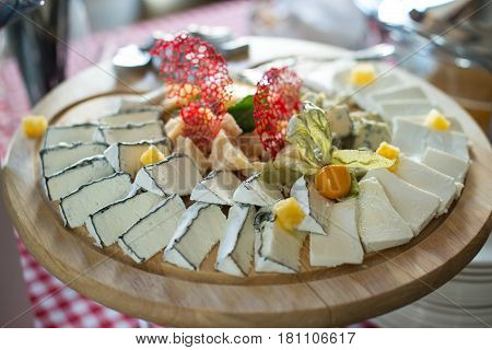 round wooden plate with different kinds of cheese honey. Top view. Brunch at an expensive restaurant