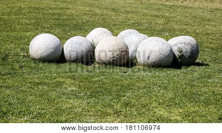Group o the round stone balls on the green grass