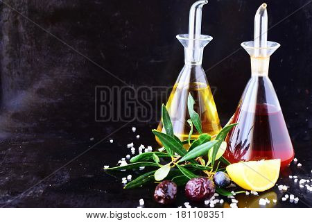 Grey abstract background with olive oil and wine vinegar glass jars with lemon, sea salt, garlic and olive branch. Space for text