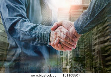 Business people shaking hands Double exposure of city