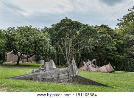 Auckland New Zealand - March 1 2017: Collection of statues in Western Park pretend to be pieces of stone facades half buried in the green lawn. Trees as background.