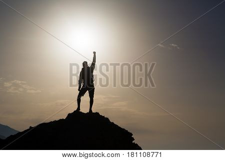 Man success with arms outstretched celebrating or praying in beautiful inspiring mountains sunrise silhouette. Man hiking or climbing with hands up enjoy inspirational landscape on rocky Crete.