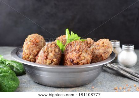 Meatballs with buckwheat in a metal bowl on a grey abstract background.Healthy food.Healthy eating concept