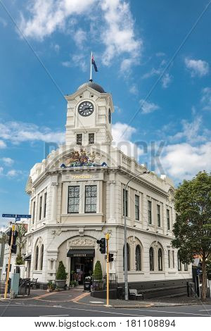 Auckland New Zealand - March 1 2017: The cream white mansion with clock tower at intersection of Ponsonby Road and College hill is a flower shop and carries British Royal crest. Street and trees.