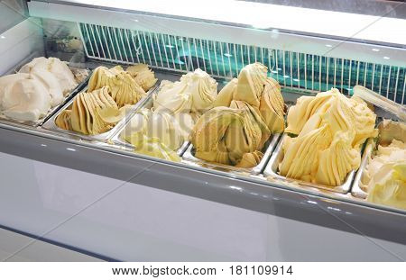 Gelato Italian ice cream mixed cream and fruits on box in electric freezer cabinet