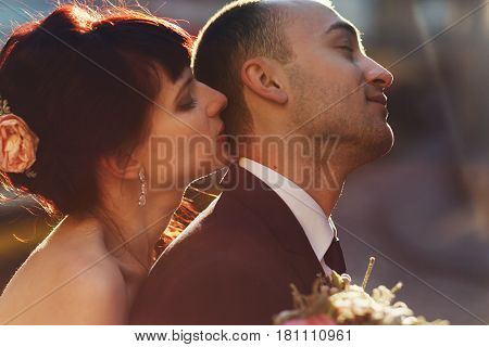 Tender Bride Kisses Groom's Head Hugging His Broad Back