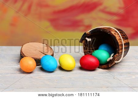 Painted Easter Colorful Eggs In Wooden Bucket At Tree Stump