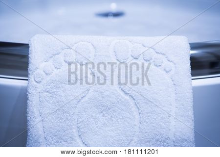 Cute white bathmat with footprints hanging over the lip of a corner shower cubicle with blue tiles in a low angle view with vignetting effect