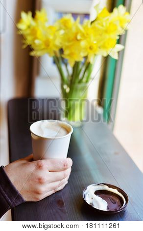 Cappuccino in a glass near the window. Hand, cappuccino, window, morning daffodils