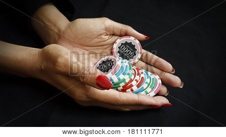Female Poker player with paint red nails hold her poker chips to make a bet on black fabric gamling and casino concept