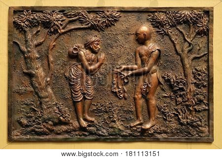 KOLKATA,INDIA - FEBRUARY 09: Gift of the half of the Devadusya (divine cloth given by Indra) to a poor Brahmin, bass relief on the wall of Jain Temple in Kolkata, India on February 09,2016.