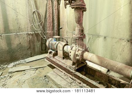 Old Rusty Pump In The Basement. Basement Of A Water Pumping Stat